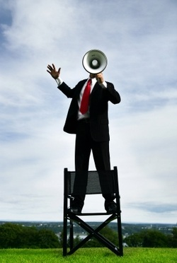 a man in black suit with white shirt and red tie shouting using a bullhorn and standing on a chair outside