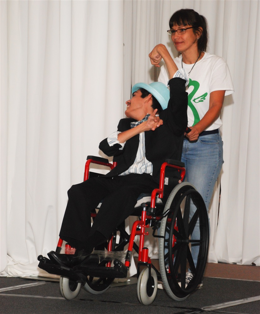 A male model in wheelchair with Runway volunteer; model wearing black suit with white shirt and light blue Fidora hat
