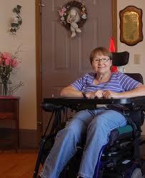 A woman in a power wheelchair inside an apartment