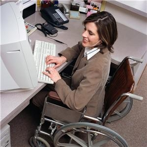 a female in wheelchair wearing suit at working station typing on computer keyboard