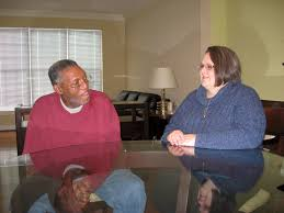 a man and woman sitting at a table appearing to talk to one another for support